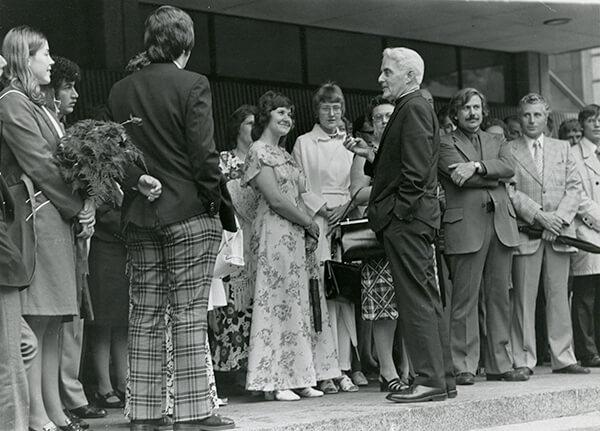 Father John Kelly speaking beside the McElcheran statue outside the Kelly Library, 1973.
