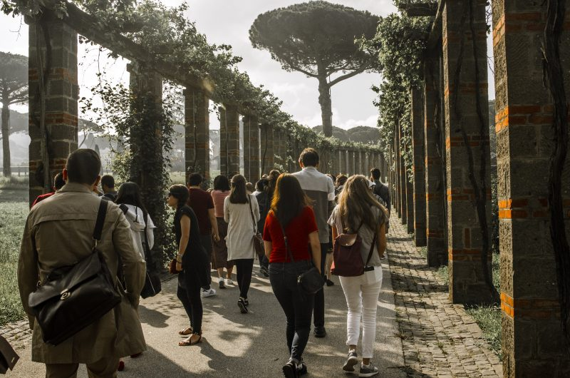 Image depicts students walking through the ruins in Italy on a Gilson trip
