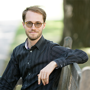 Image Depicts professor Jean- Oliver Richard sitting on a bench on the St.Michael's college campus