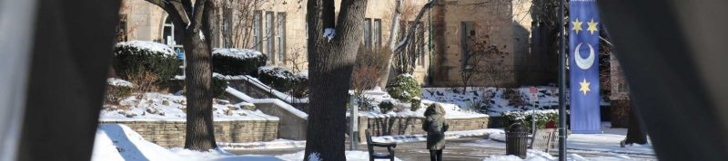 Image depicts a student walking towards Brennan Hall