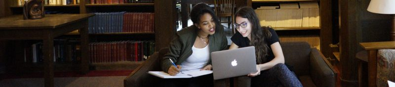 Image depicts two females studying in together in the library