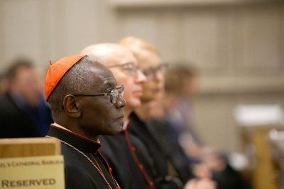 Image depicts Cardinal Sarah listening in the Cathedral