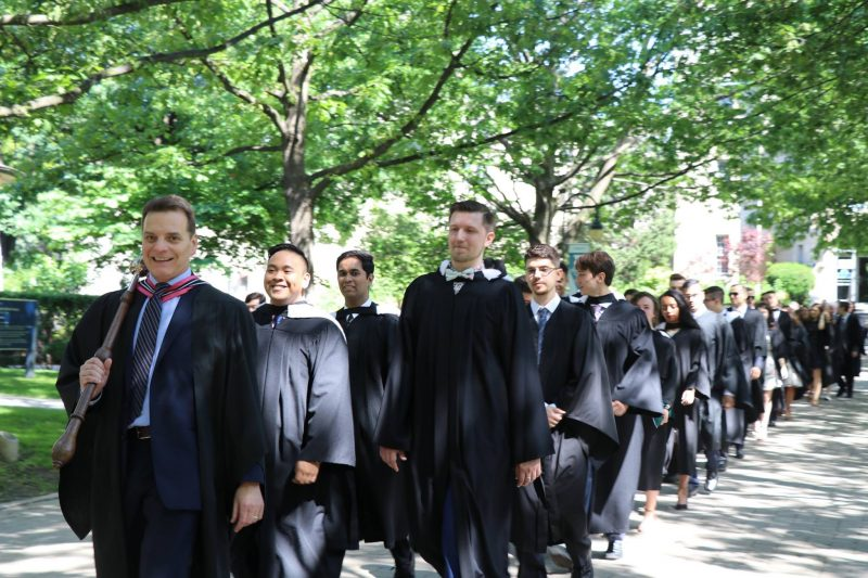 Image depicts students dressed in convocation robes walking to convocation hall lead by Dean of Students Duane Rendle