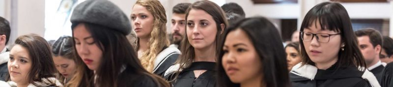 Image depicts student dressed in convocation robes sitting in convocation hall