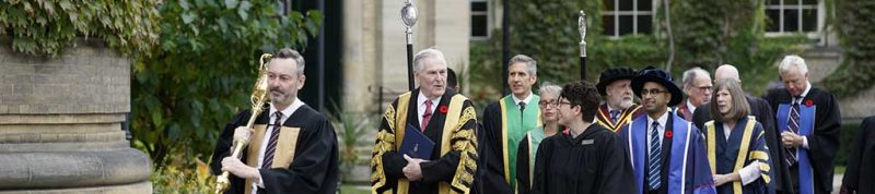 Image depicts UofT and USMC staff walking into Convocation hall for Convocation