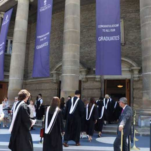 Image depicts students dressed in convocation gowns walking into convocation hall