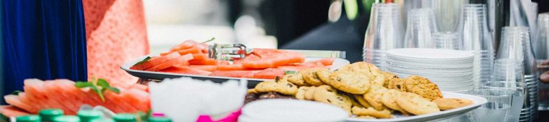 Image depicts a try of cookies and fruit on a nicely dressed table