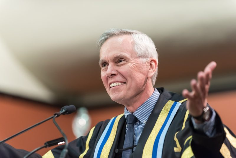 Image depicts President David Mulroney addressing students at convocation