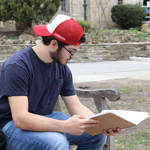Image depicts a student sitting on a bench in the USMC Quad reading notes