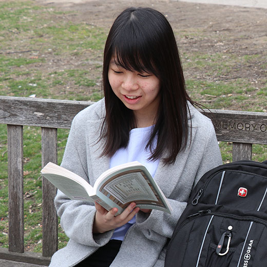Image depicts a student sitting on bench in the USMC quad reading a book