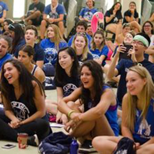 Image depicts students dressed in orientation shirts sitting in Alumni Hall cheering
