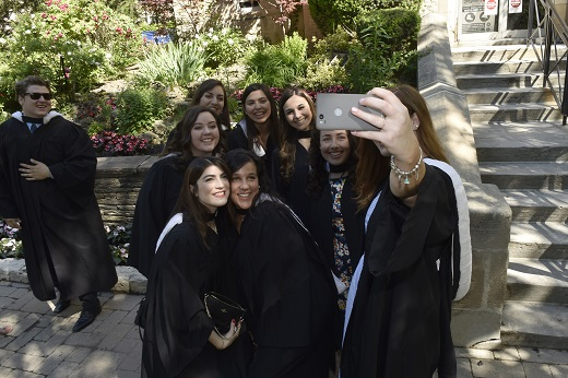 Image depicts graduates taking photos after the graduation ceremony