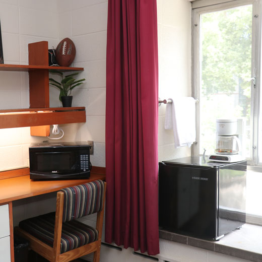 Image depicts the inside of a residence room. It shows a curtain, a coffee maker, a microwave and a desk with a chair