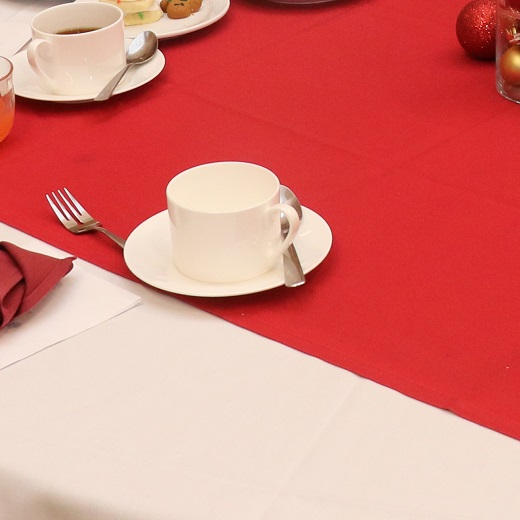 Image depicts a nicely set table with a coffee cup on a table cloth
