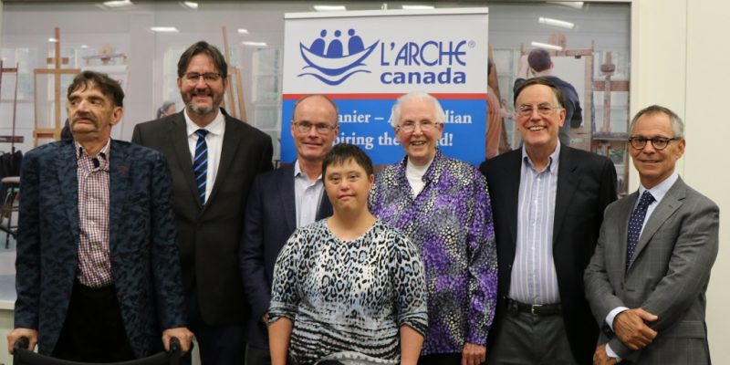 Image depicts a group of people standing in front of a banner for L'arche Canada