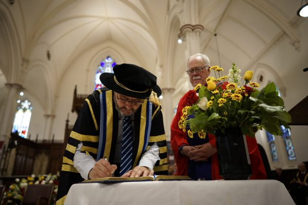 Dr. David Sylvester signs the registry after becoming president of St. Michael's.