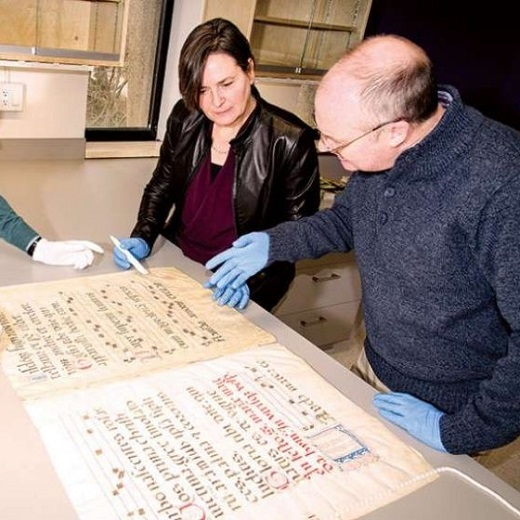 Image depicts people looking at an old page from a manusript on the Kelly Library Conservation Tour