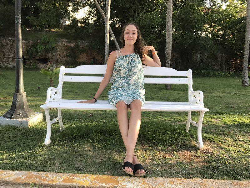 Orientation Executive Taylor Medeiros sits on a bench.