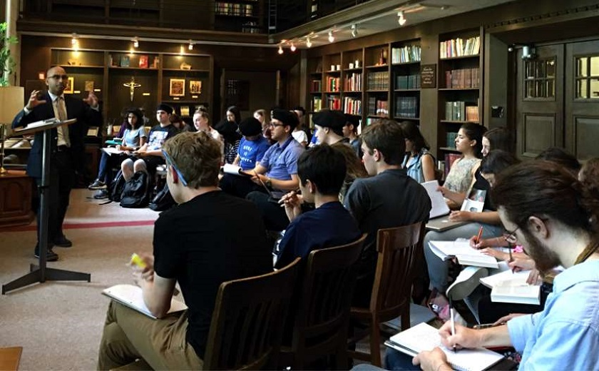 Image depicts Principal Randy Boyagoda teaching a seminar in the Shook common room