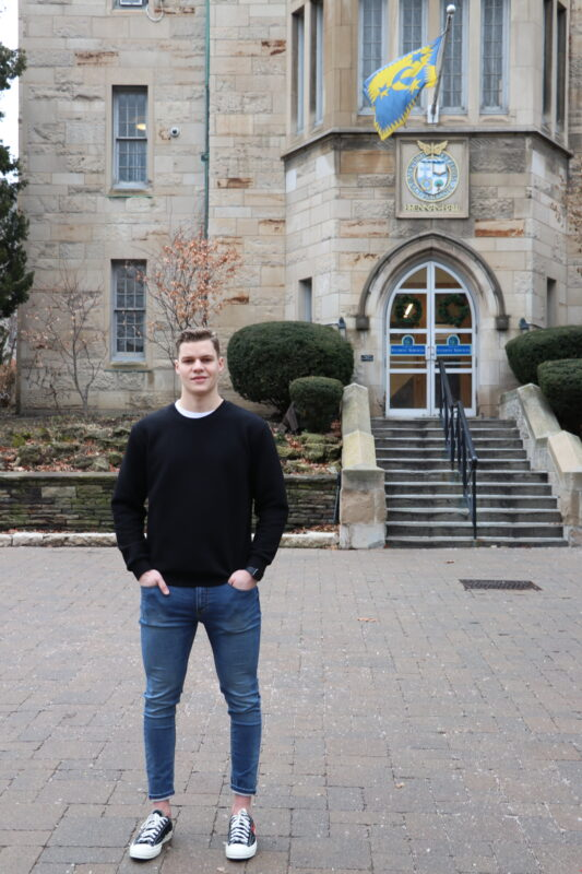 St. Mike's student athlete Kyle Potts stands in front of Brennan Hall on campus.