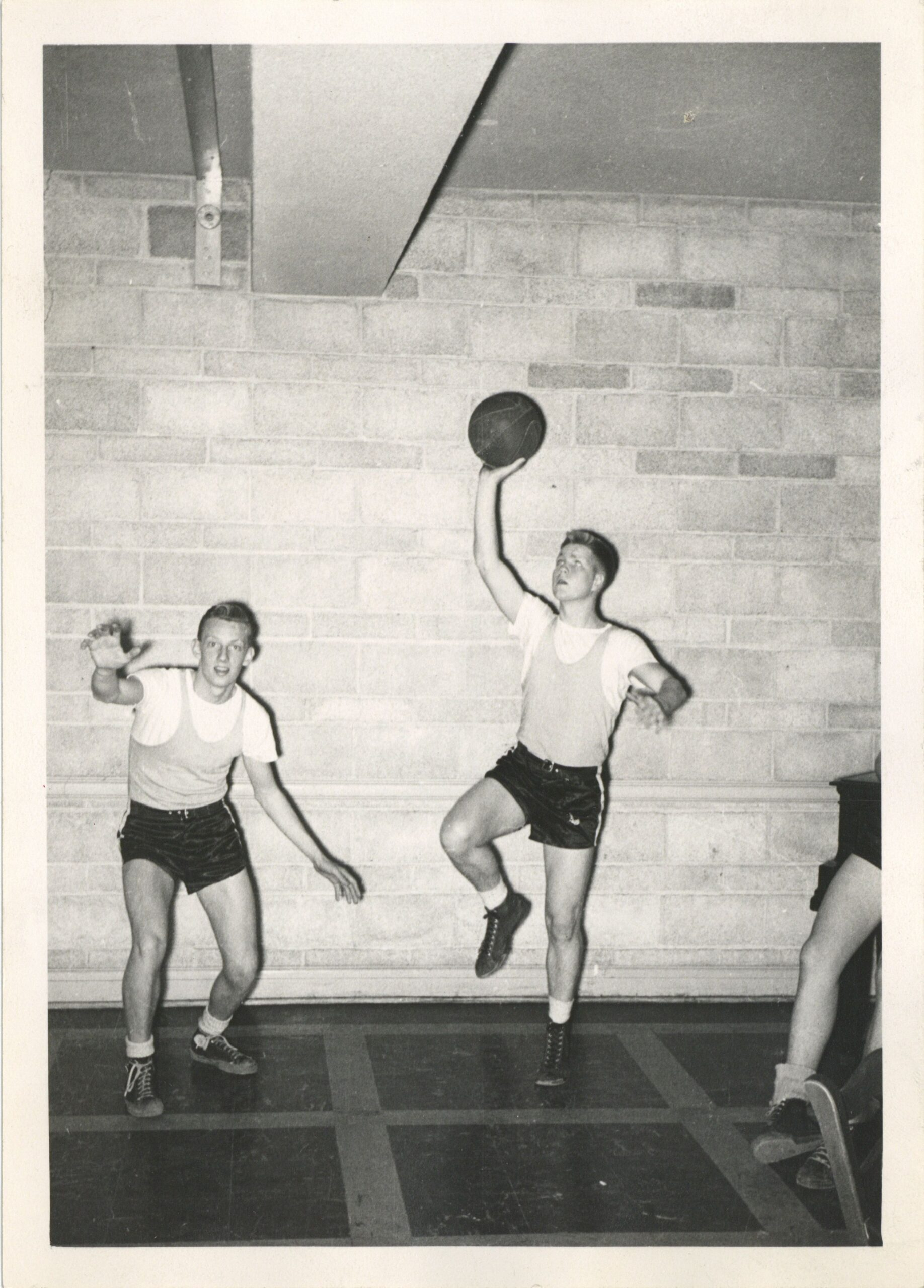 Image depicts a black and white photo of men playing indoor basketball