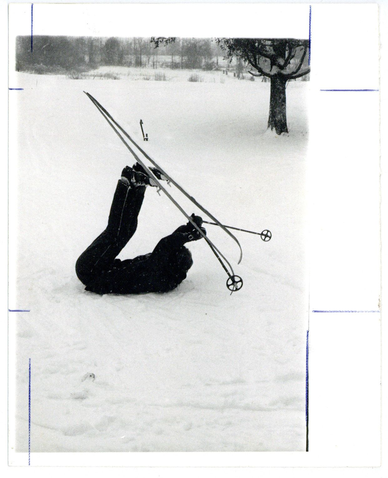 Image depicts a black and white photo of a person who has fallen down while skiing