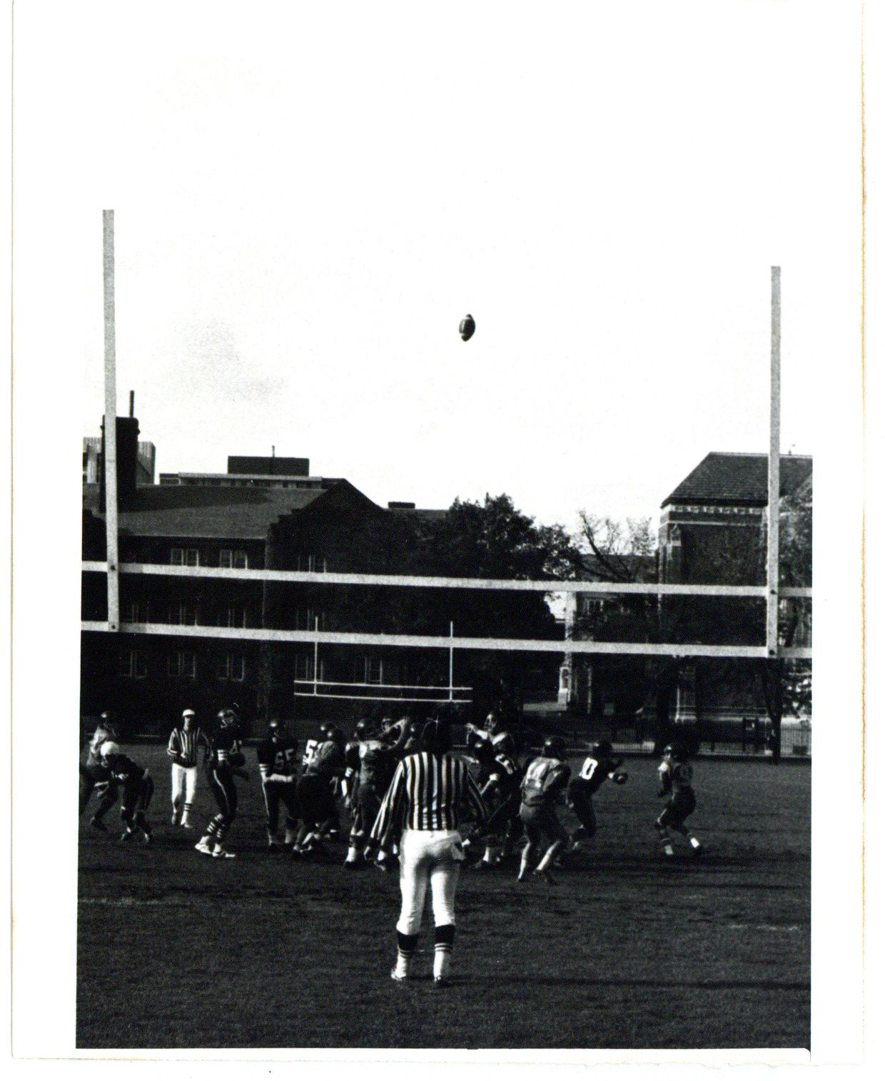 Image depicts a black and white photo of a football game on campus