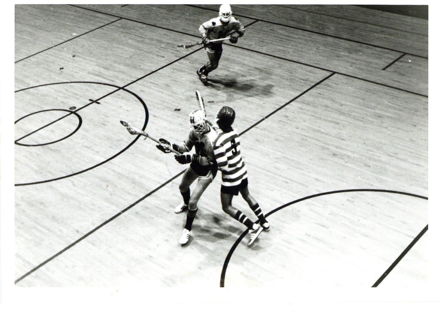 Image depicts a black and white photo of people playing lacrosse