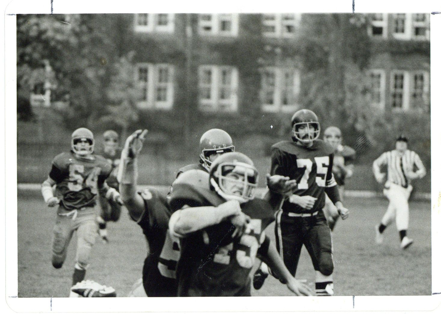 Image depicts a black and white photo of a football team celebrating a touchdown