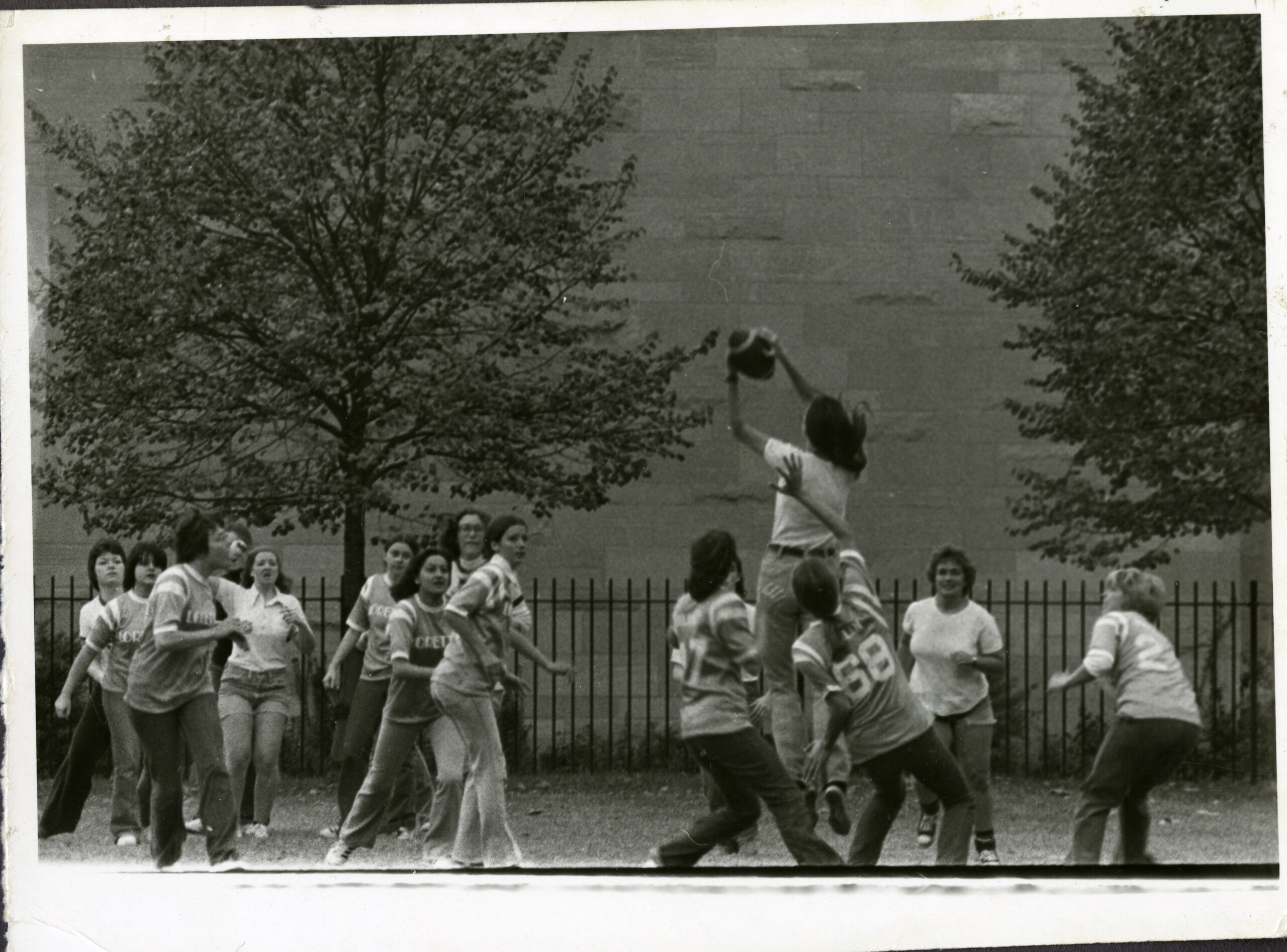 Image depicts a black and white photo of males and females playing basket ball