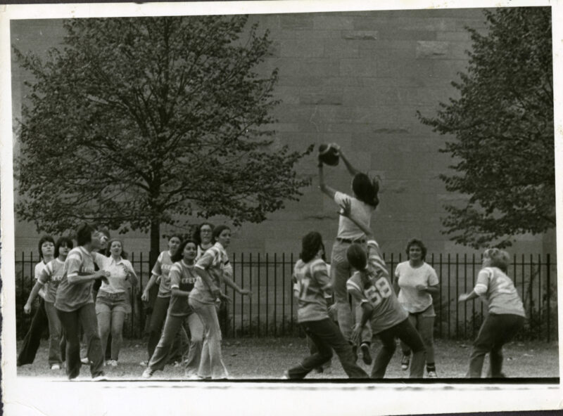Women play football on campus in this archival image from the early 1970s.