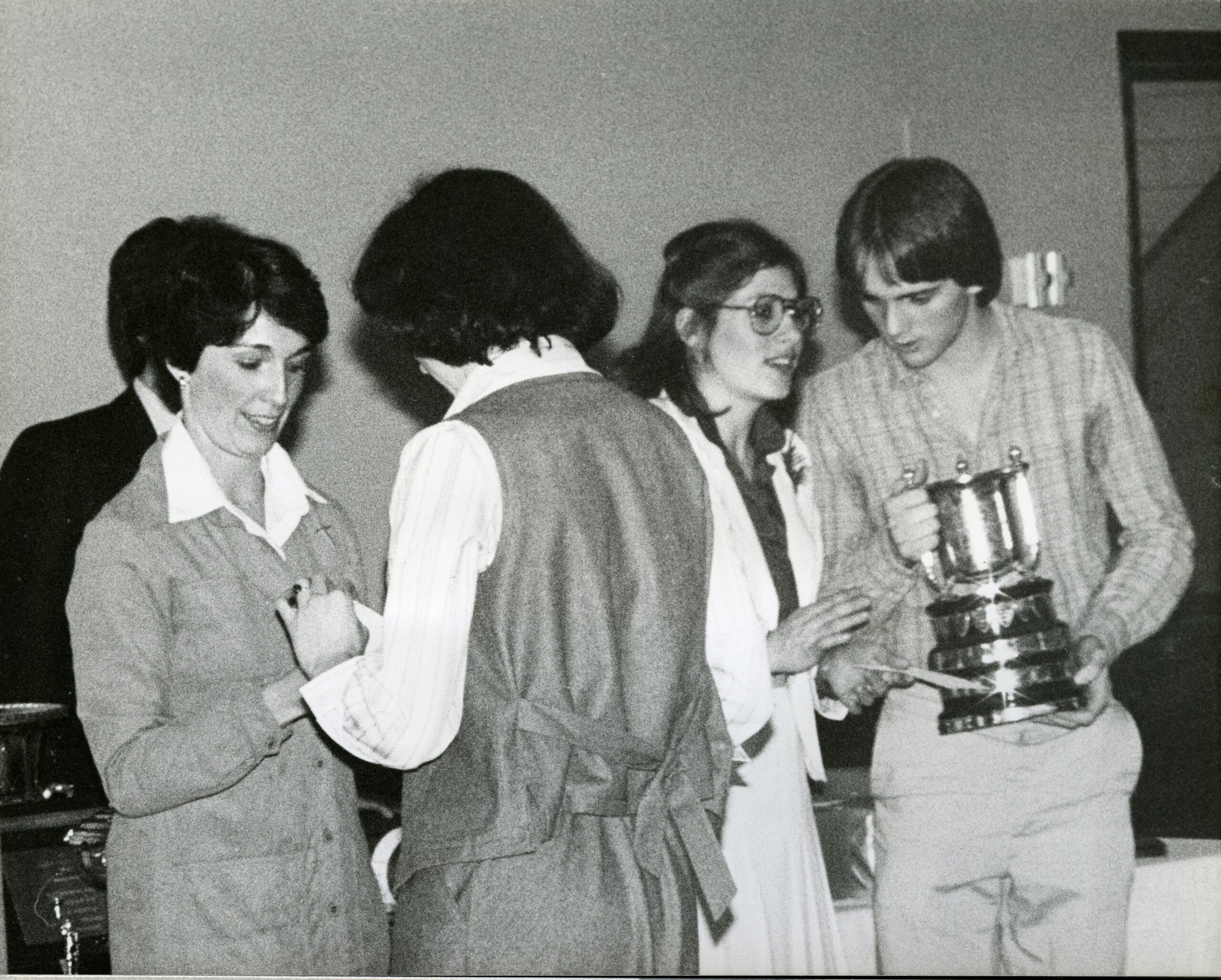 image depicts a black and white photo of males and females receiving awards