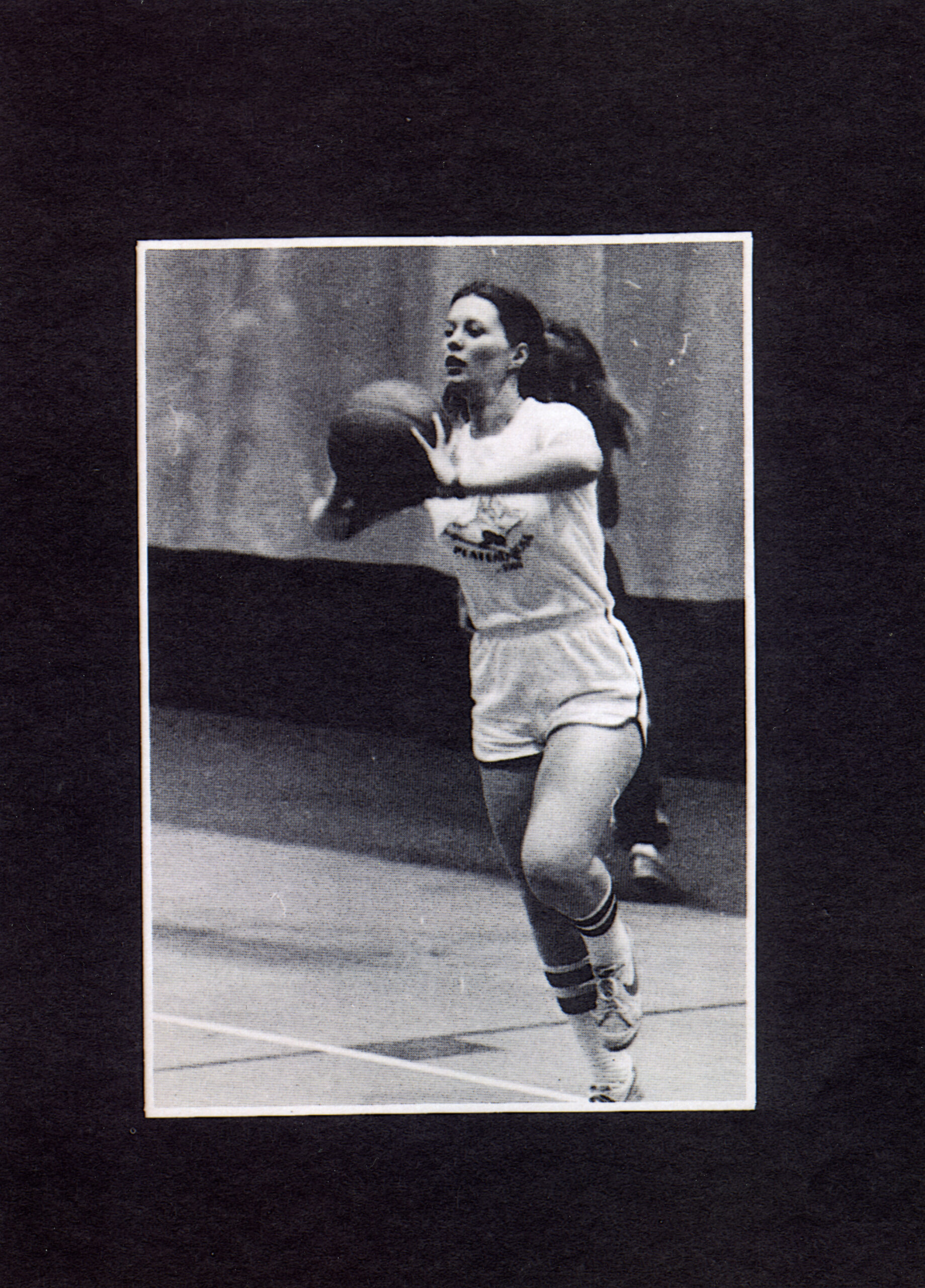 Image depicts a black and white photo of a female playing basketball