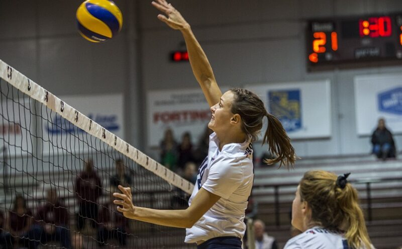 Student athlete Anna Licht blocks at the net during a match.