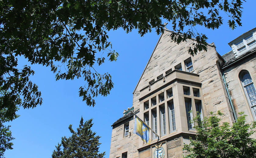 Image depicts the southern facade of Brennan Hall on a sunny summer day.