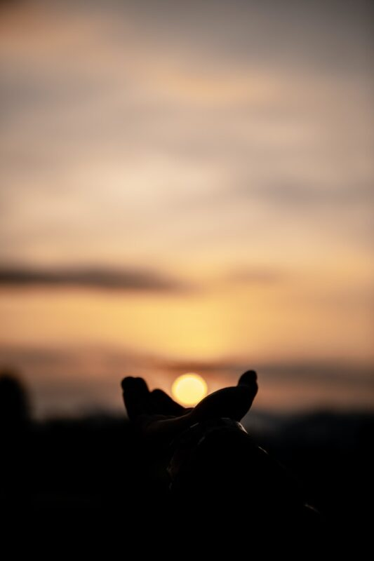 Image shows a person cupping their hands against the sky, creating the illusion that they are holding the setting sun