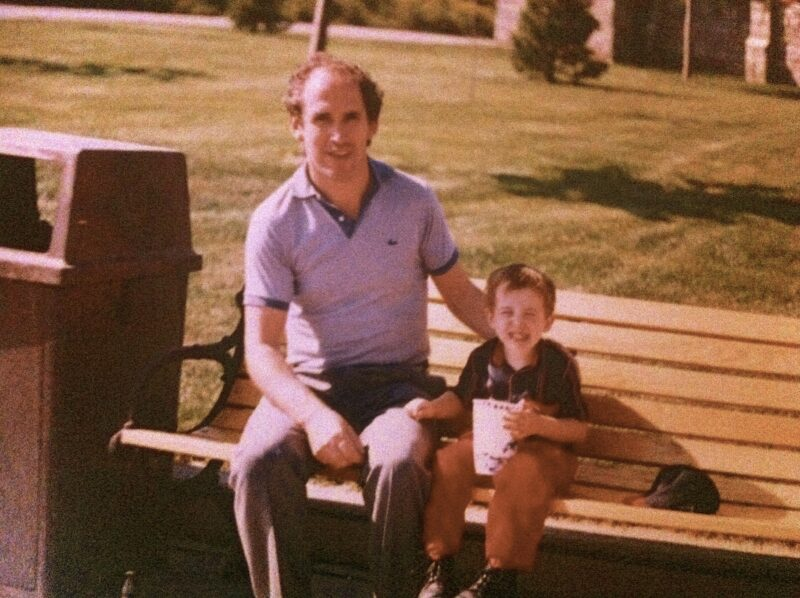 Vintage image depicts a man sitting next to his young son on a park bench. The son is holding a large drink in a takeout cup.