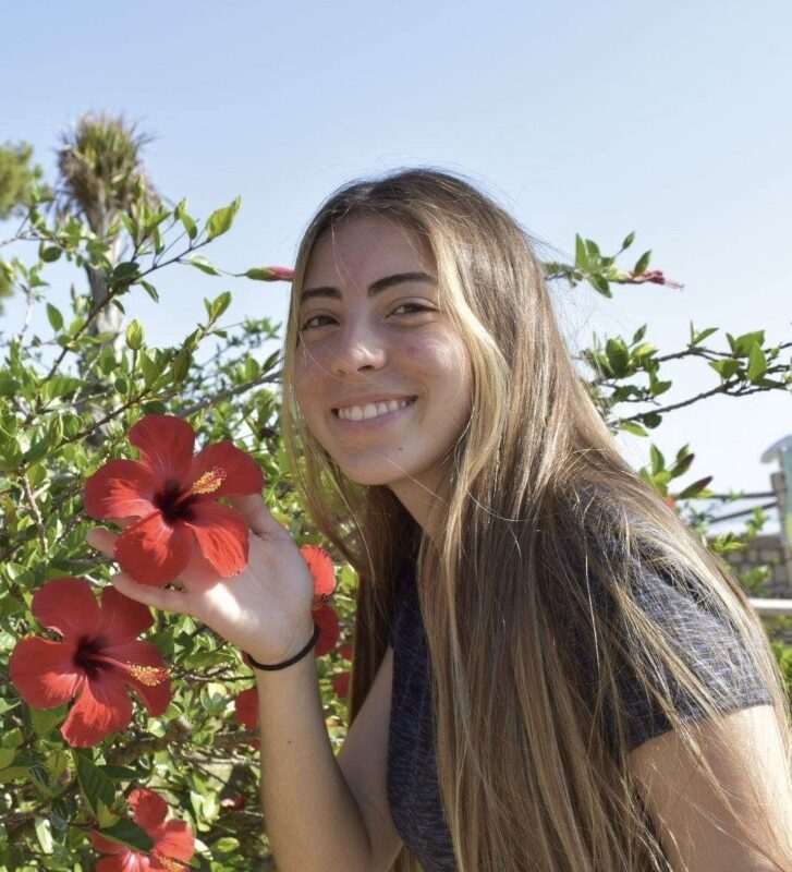 Image depicts USMC student Anna Zappone, posing next to a bush of flowers.