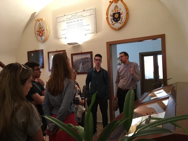 Image depicts Dr. Adam Hincks, SJ speaking to a group of St. Michael's students during a tour of the Vatican Observatory.