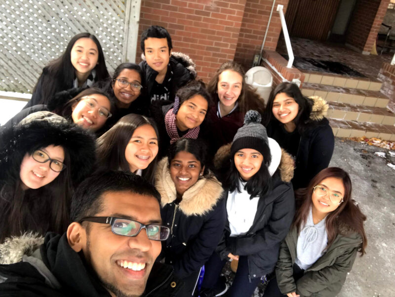 Image depicts MRE student Andrew Selvam taking a selfie with a group of students.