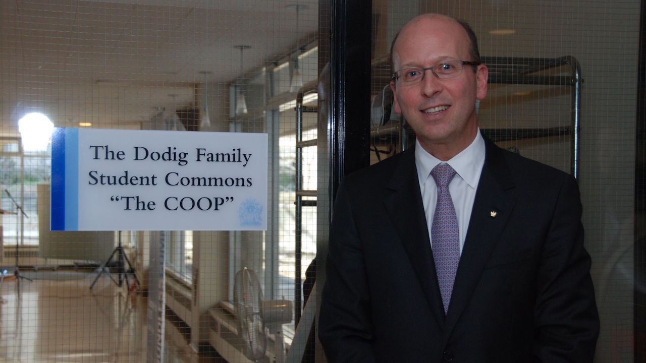 Image depicts alumnus Victor Dodig standing next to a sign for the Dodig Family Student Commons (known as the Coop) in Brennan Hall on the St. Michael's campus.