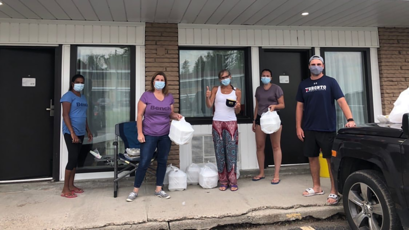 Image depicts a group of people in medical masks standing under an awning, with St. Michael's student Curtis Harvey at the right