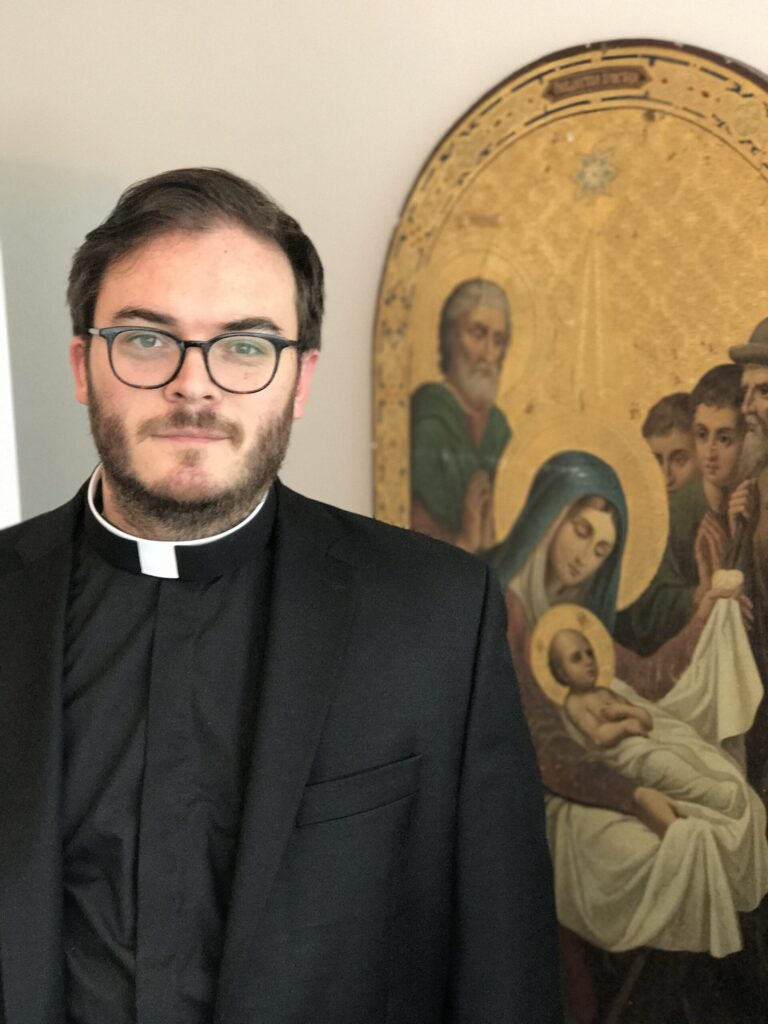 Image depicts Fr. Alexander Laschuk standing in front of an icon