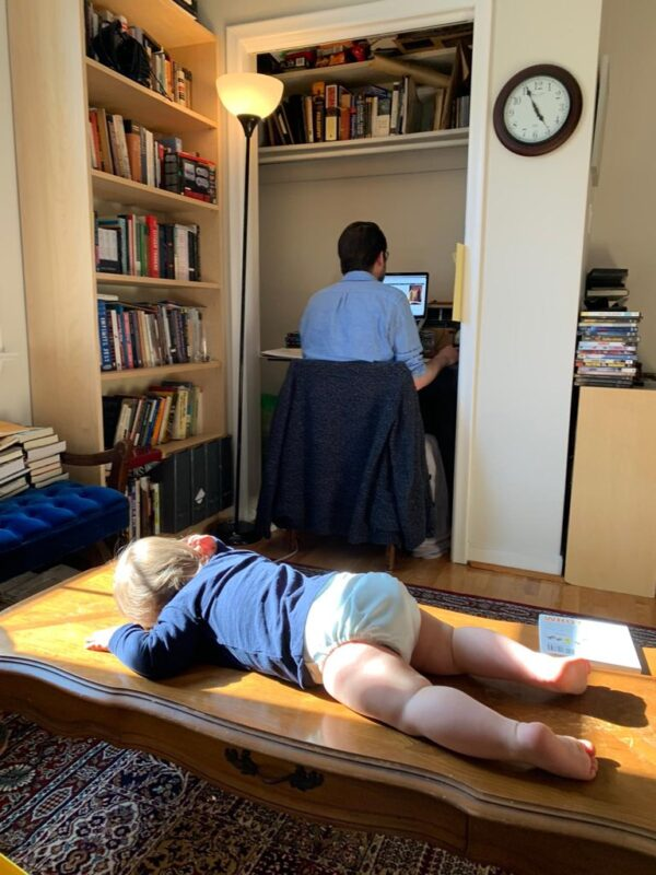 A toddler rests face-down on a coffee table facing a man working at a desk in a closet.