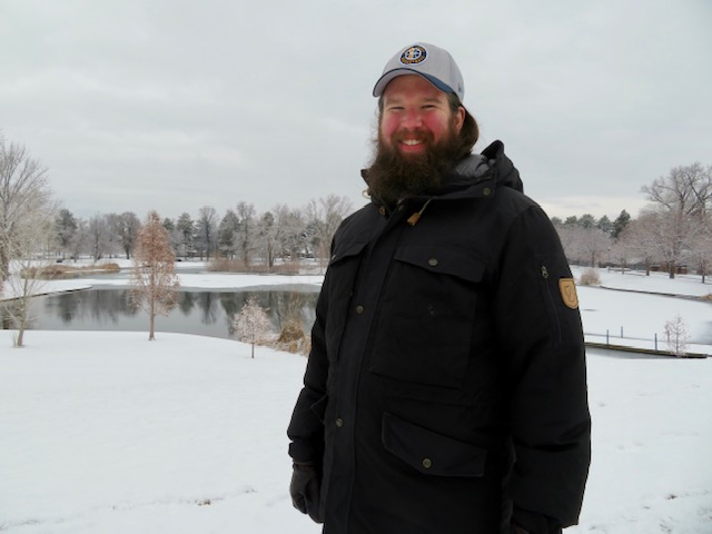 Image depicts Dr. Sean Argondizza-Moberg standing outdoors on a snowy day in a winter coat