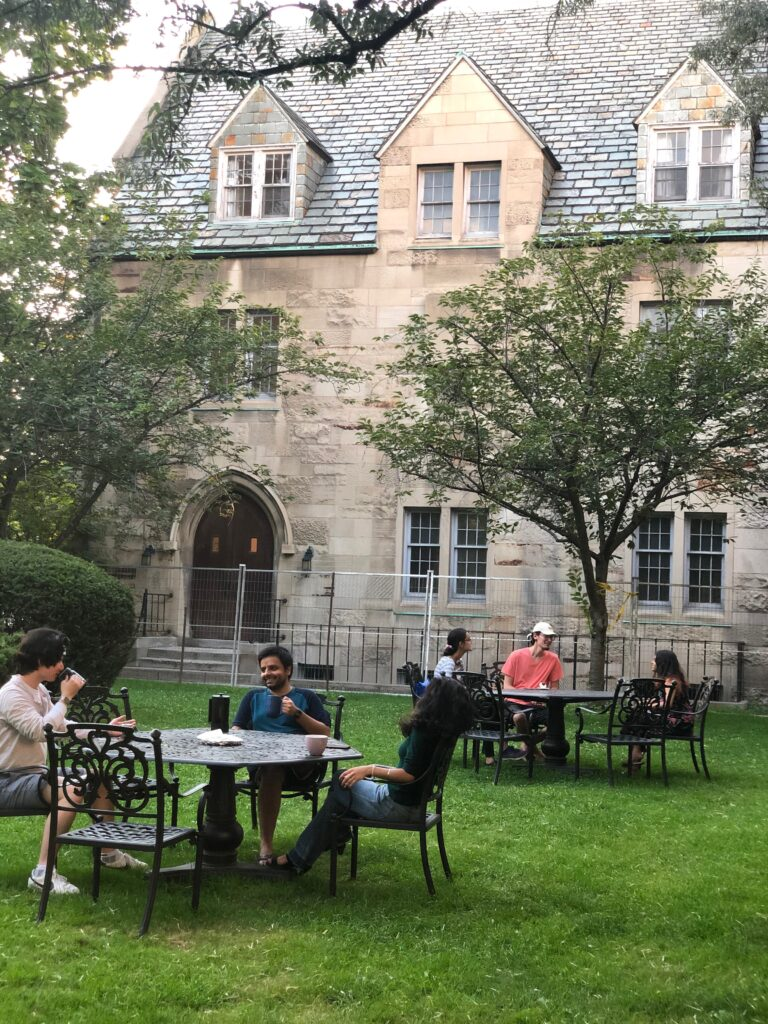 Students sit together at outdoor tables in a small parkette at St. Michael's