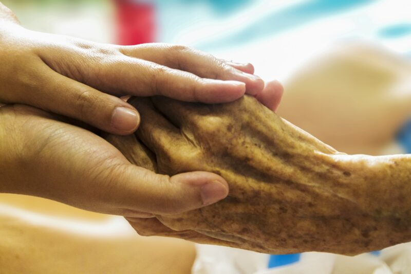 A hospice caregiver clasps the hands of an elderly patient