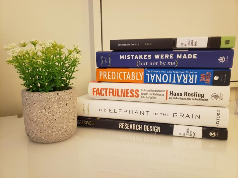 Photograph of Risa's books: Extraterrestrials; Mistakes Were Made (But Not By Me); Predictably Irrational; Factfulness; The Elephant in the Brain; Research Design
