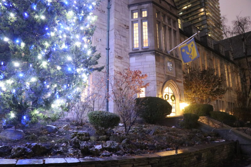 A tree lit up for the holidays next to Brennan Hall