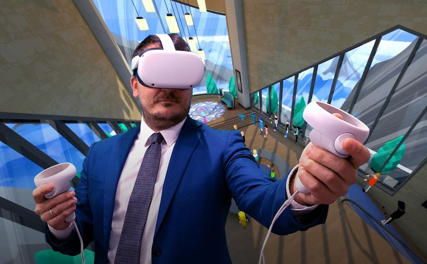 St. Mike's prof Paolo Granata stands in a VR headset in front of a background depicting a virtual learning space